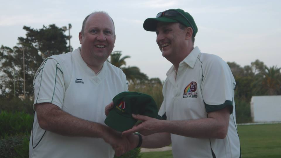 Marsa skipper Tim Wheeler gratefully receives a Graces CC cap from his counterpart Dominic Scott